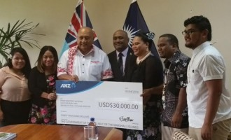 Minister Receives $USD30,000 For PM's Disaster Relief Fund