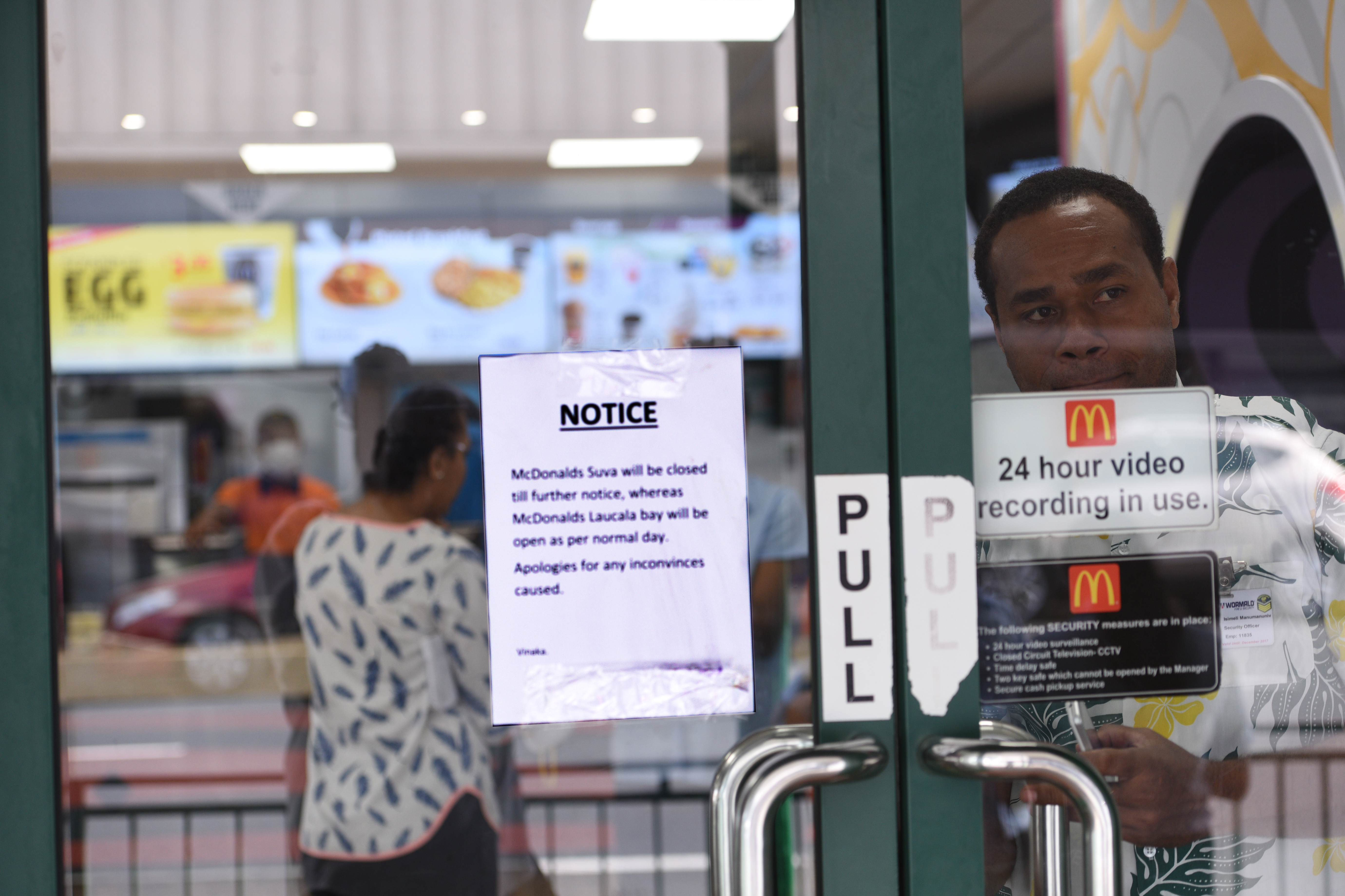 A security officer mans the closed door at MacDonalds with sales attendants wearing safety masks due to the asbestos scare  in town on Friday June 2nd, 2017. Photo:Jone Luvenitoga