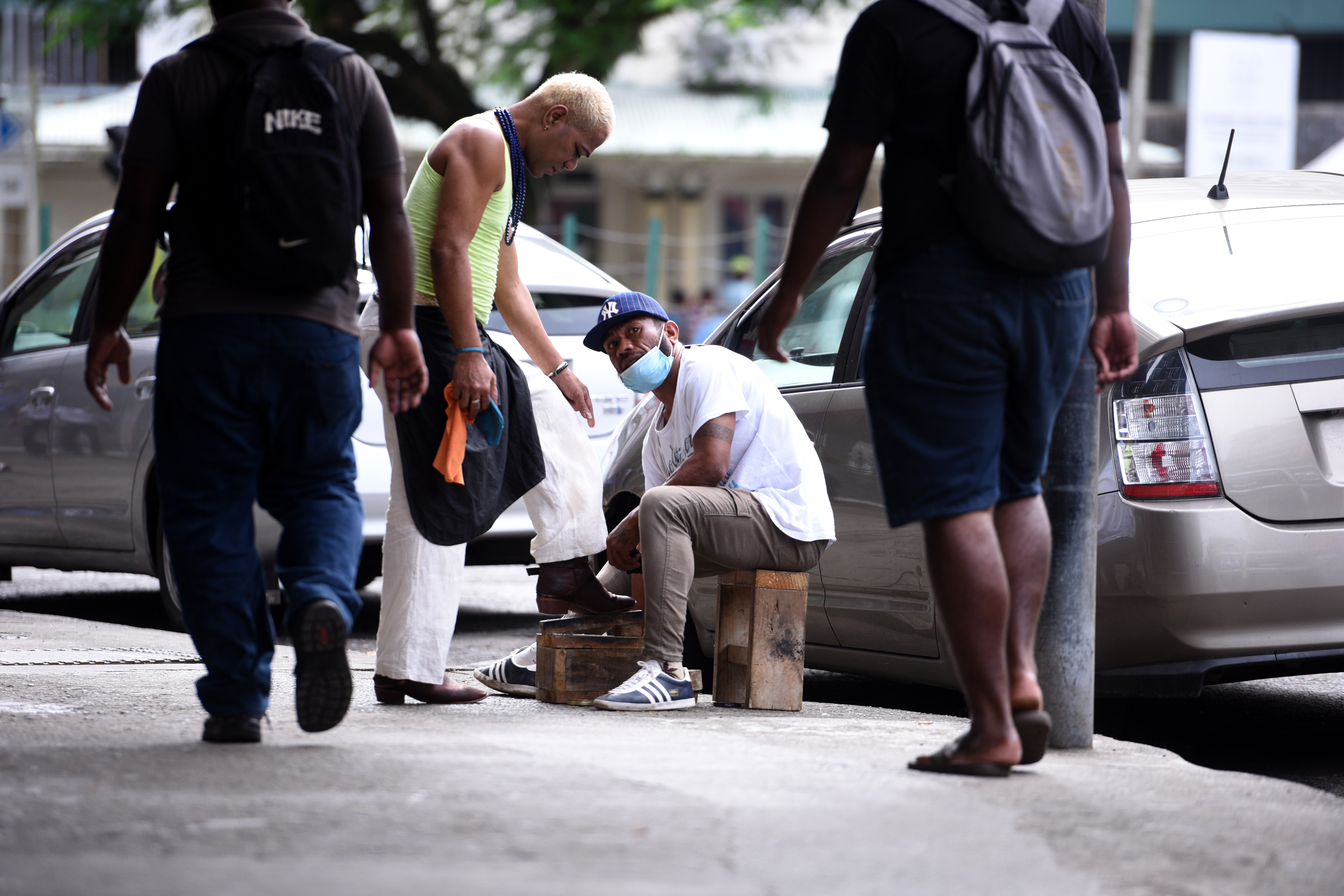A shoeshine boy has his mask on while dgoing about his business along Scotts St in Suva on Friday June 2nd, 2017. Photo:Jone Luvenitoga