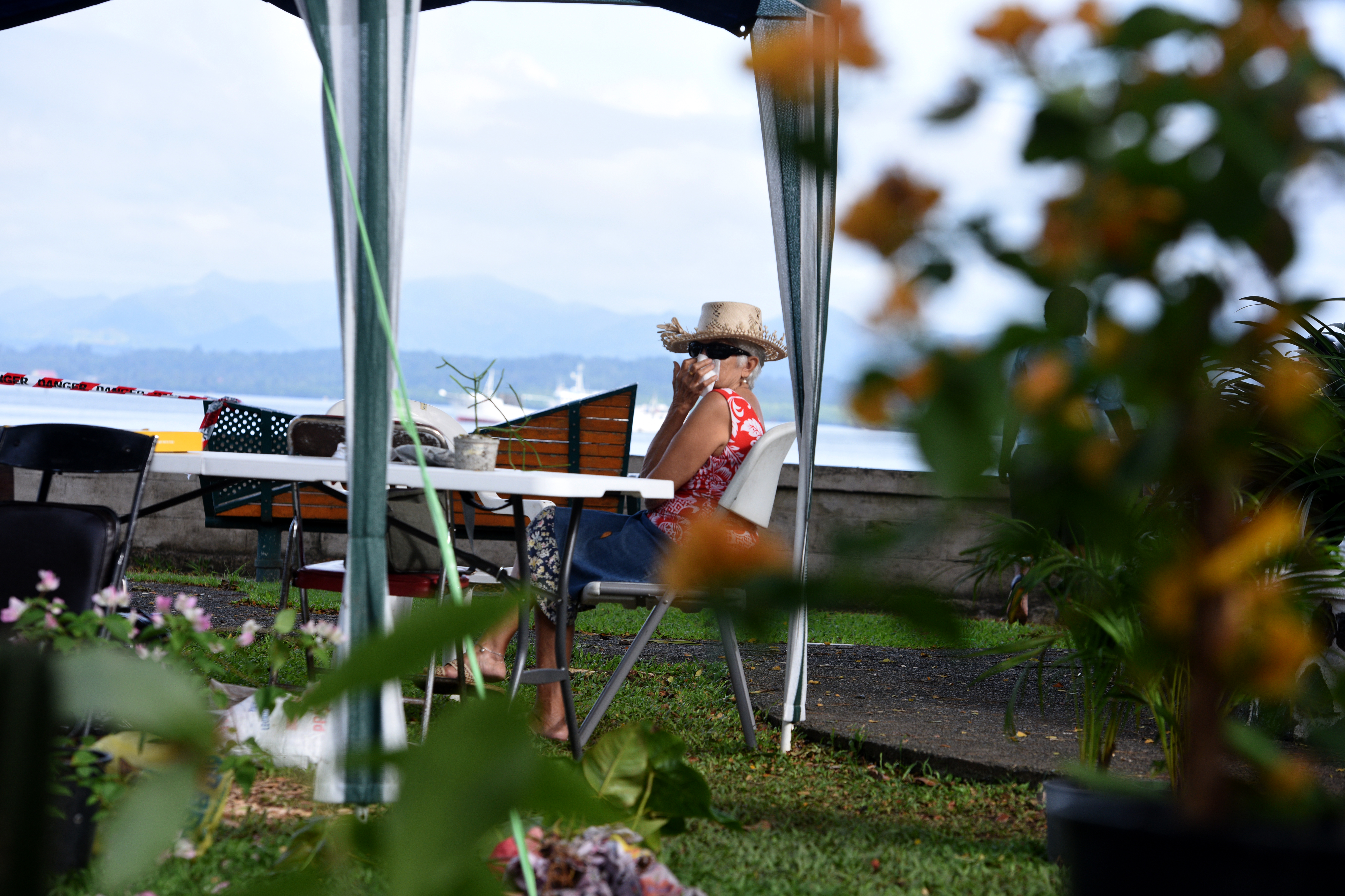 A woman selling pot plants on the Civic Center foreshore covers her nose with a hankerchief while waiting for evacuation on Friday June 2nd, 2017. Photo:Jone Luvenitoga