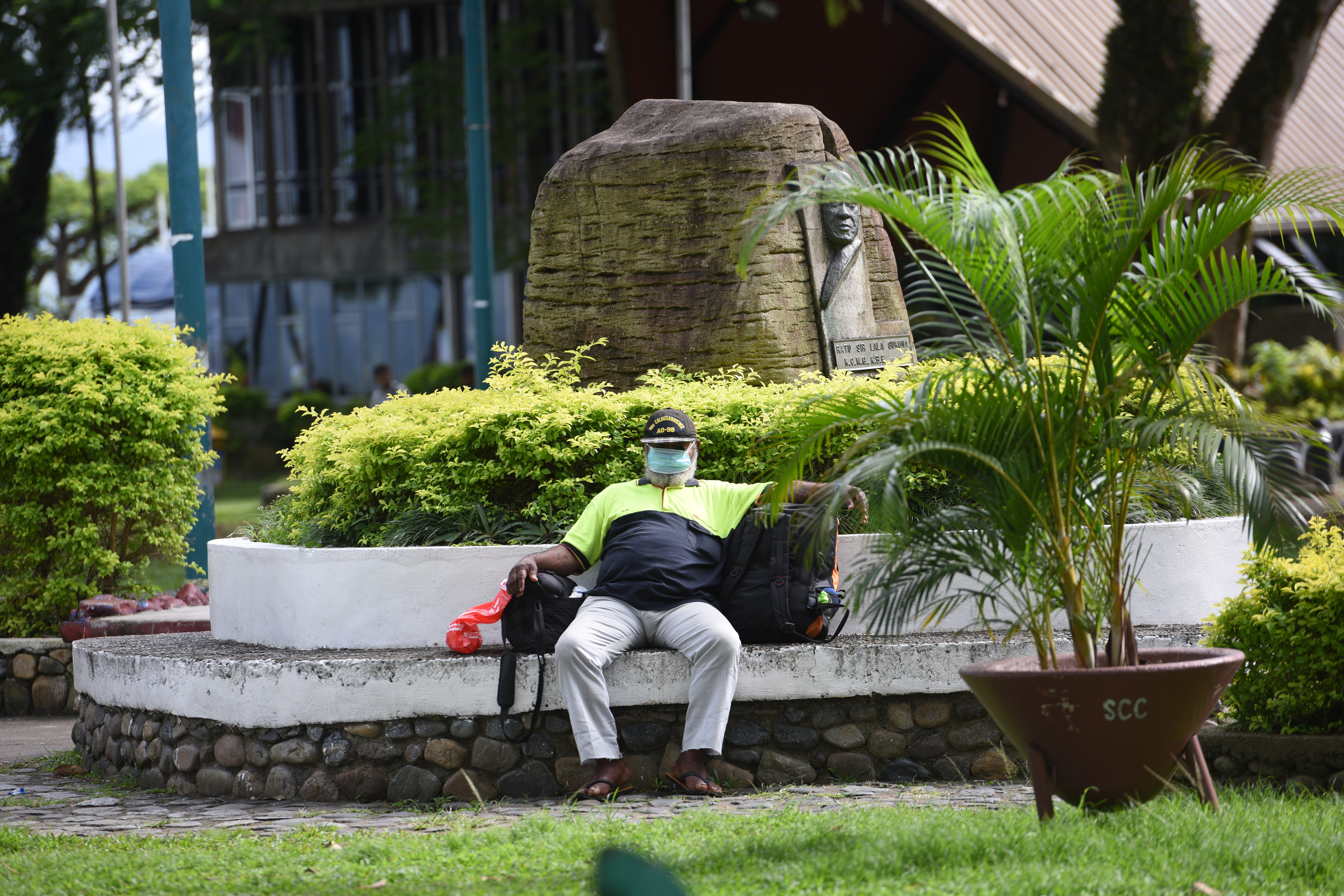 A homeless man sits on one of the monuments at Sukuna Park in Suva with his safety breathing mask. Photo:Jone Luvenitoga