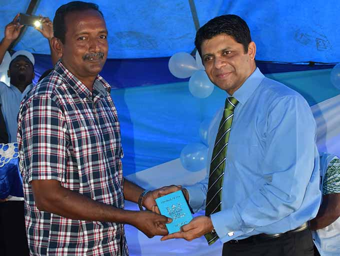 Amrit Prasad (left), receives his passport from the Attorney General Aiyaz Sayed-Khaiyum in Labasa on June 1, 2017.  Photo: Josaia Ralago