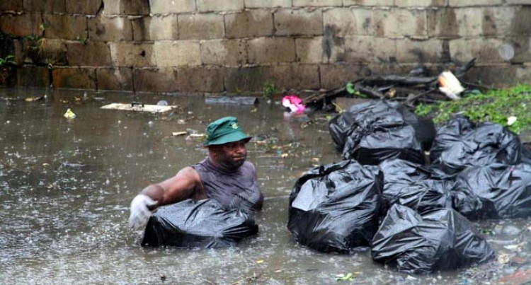 Pastor Jumps Into  Waterway To Clear Rubbish In  Heavy Downpour