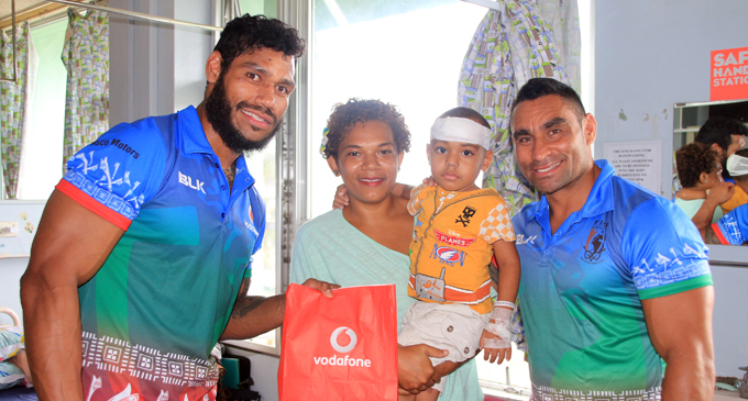 Former NRL star Sisa Waqa (left) and James Storer(right) reach out to a sick child at Colonial War Memorial Hospital, Suva on October 5,2017. Photo: Vodafone Fiji