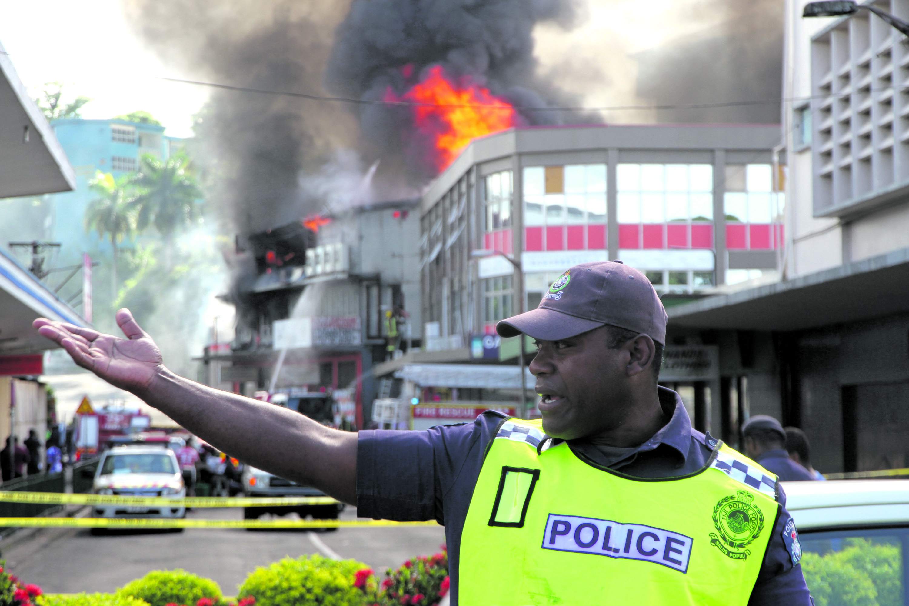 A Police officer on crowd control while firefighters battle the blaze at the J. Santa Ram Supermarket bulk store and Lotus Garment building at Robertson Road in Suva on December 9, 2017.