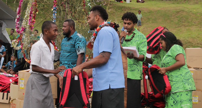 "Wallaby centre Samu Kerevi presents ""Back to School Backpacks"" to a Koro Island student on December 21, 2017. Photo:  Ministry of Youth  and Sports."