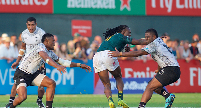 Seabelo Senatla fends off Vatemo Ravouvou in the Cup semifinal of the Dubai 7s on December 3, 2017. Photo :Ian Muir