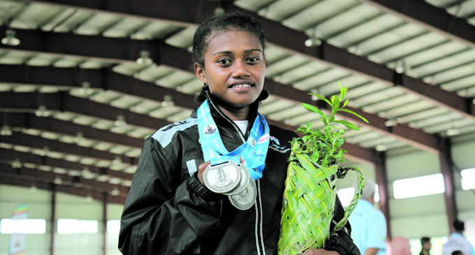 Team Fiji Women's 48kg category weightlifter Seruwaia Malani shows her spoils during the Pacific Mini Games wieghtlifting competition at Epauto Hall, Port Vila, Vanuatu on December 5, 2017. Photo :Peni Komaisavai.