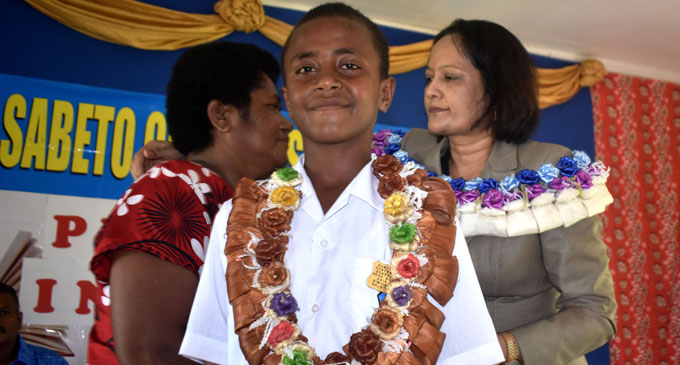 Simione Nadolo after being inducted as headboy while Minister for Health and Medical Services, Rosy Akbar comforts his mother, Siteri Liku, during the Sabeto Central School prefect induction ceremony in Nadi on February 1, 2018. Photo: Arieta Vakasukawaqa