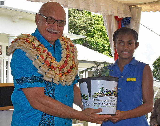 Hilton Special School headgirl Seruwaia Marama hands a pot plant to President Major-General (Ret'd) Jioji Konrote before the launching of the 2018 International Day of Forests at Borron House on March 21, 2018.  Photo: DEPTFO News