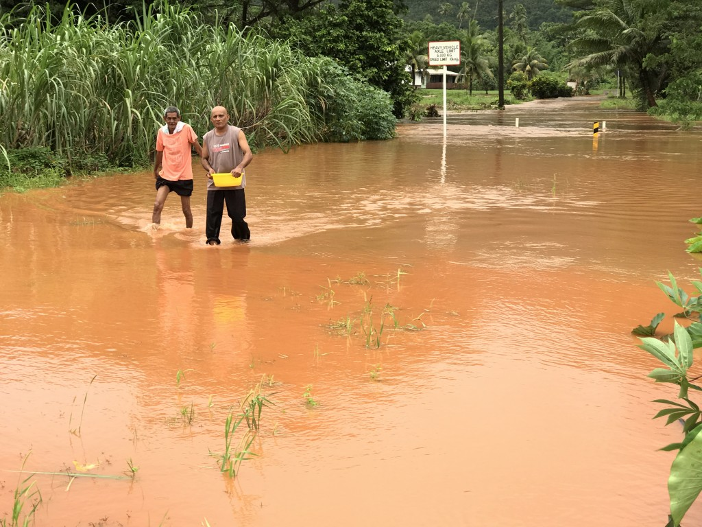 Amrika Prasad and Virendra Lal crossing flooded road near VuniVau Village in Labasa on April 10. Photo Shratika Naidu.