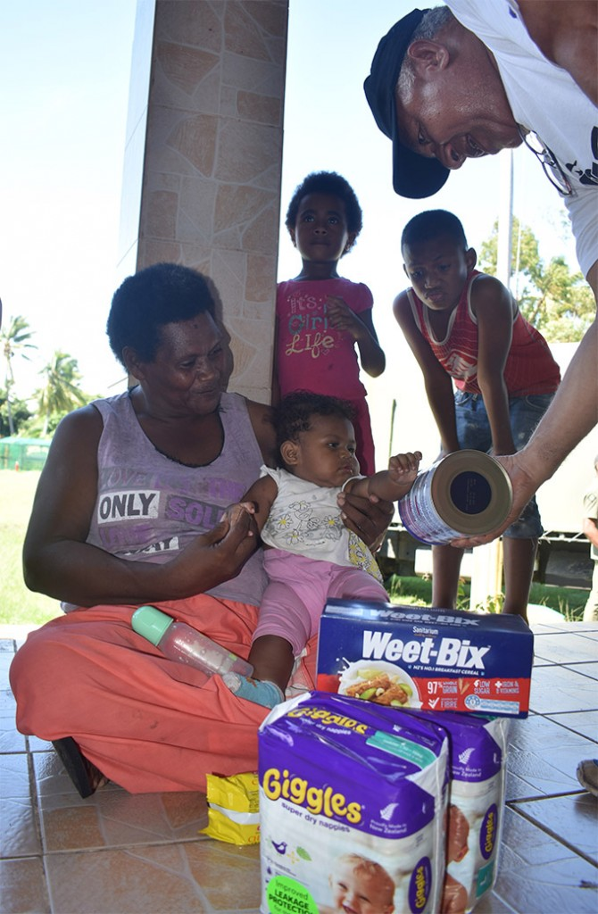 Prime Minister Voreqe Bainimarama hands over rations to Amelia Tulo, and her granddaughter Analaisa Tuwai at the evacuation centre at Tavua District School on April 11, 2018.   Photo: Waisea Nasokia
