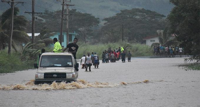 Vehicle and public tries to cross a flooded Sabeto junction in Nadi yesterday. Photo: WAISEA NASOKIA