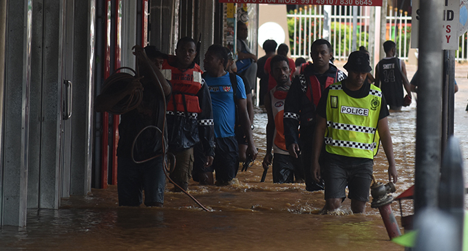 Police officers and members of the public patrol a flooded Nadi Town yesterday. Photo: Waisea Nasokia