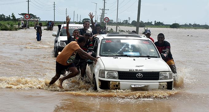Sabeto youths push a vehicle through floodwaters at Waimalika, Nadi, yesterday. Photo: Waisea Nasokia