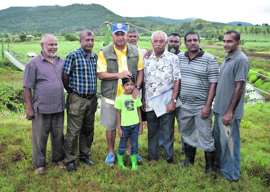 Prime Minister Voreqe Bainimarama (middle) with farmers and five year old Mohit Khan during his visit to Korotari in Labasa on May 2. The background is showing the Korotari foot bridge. From Left: Mohammed Ali, Satish Chand, Suresh Kumar, Mohammed Wahid Khan, Mohammed Khan, Mohammed Hussain and Mukesh Lal. Photo: Shratika Naidu