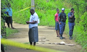 A team of Police officers at the crime scene where Asbin Nair was found dead just a few metres away from his home in Jubaraki Settlement in Olosara, Sigatoka, on June 7, 2018. Covered in carton cuttings are the blood trails which led to where the body was found. Photo: Arieta Vakasukawaqa