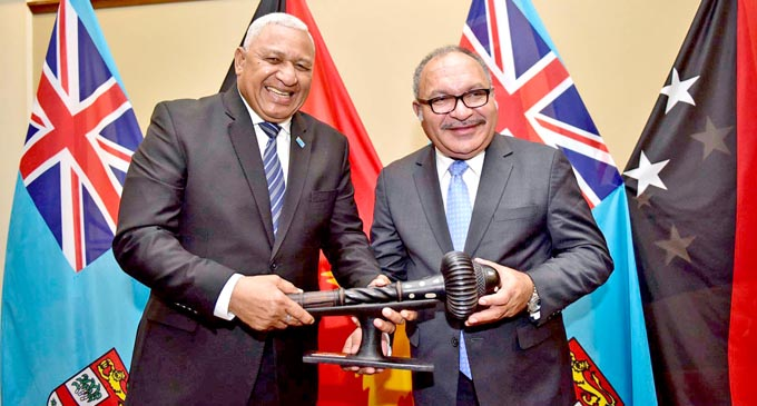 Welcome, PM O'Neill... Prime Minister Voreqe Bainimarama presents a traditional war club replica to Papua New Guinea Prime Minister Peter O'Neill as a token of appreciation at the Grand Pacific Hotel in Suva on July 8, 2018. Mr O'Neill was greeted with full military and traditional ceremonies as he arrived for an official visit. Photo: DEPTFO News
