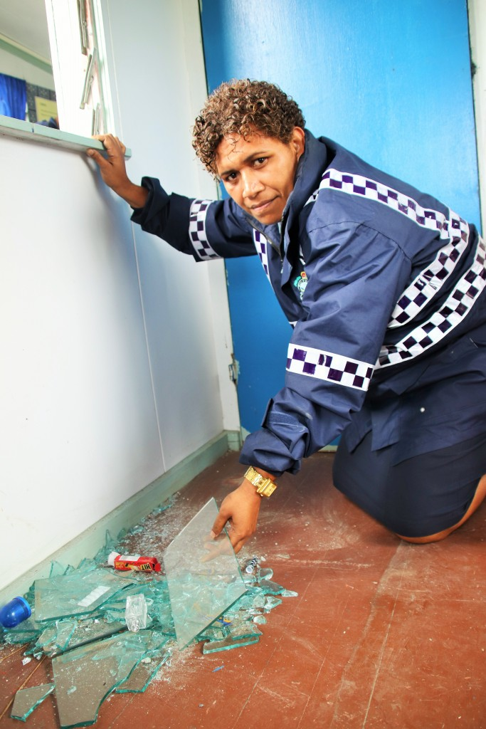 Special Constable Julie Tuikenawa clears the broken windows at the Police Community Post.