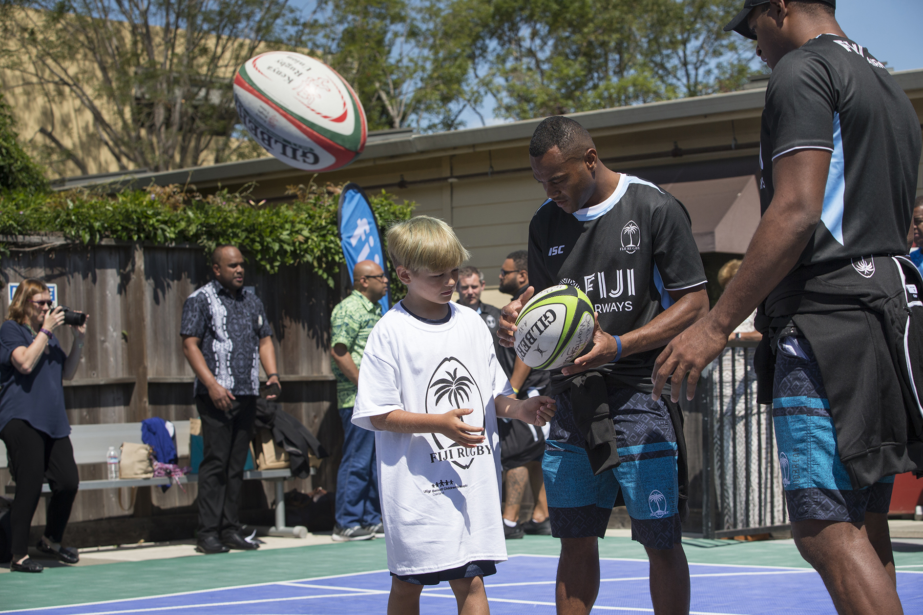 Fiji Airways Fijian 7s rep Alasio Naduva teaching a young fan Brody Tatman how to pass at UCSF Benioff Children's Hospital in Oakland on July 19, 2018.   Photo:  Zimbio