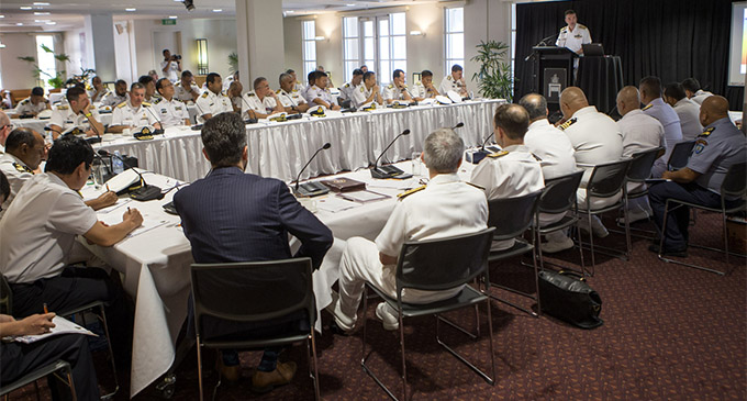 Senior naval officers from Exercise Kakadu participating nations listen to Commander Australian Fleet, Rear Admiral Jonathan Mead, AM, RAN, deliver his keynote address at the Northern Territory Legislative Assembly Building in Darwin.