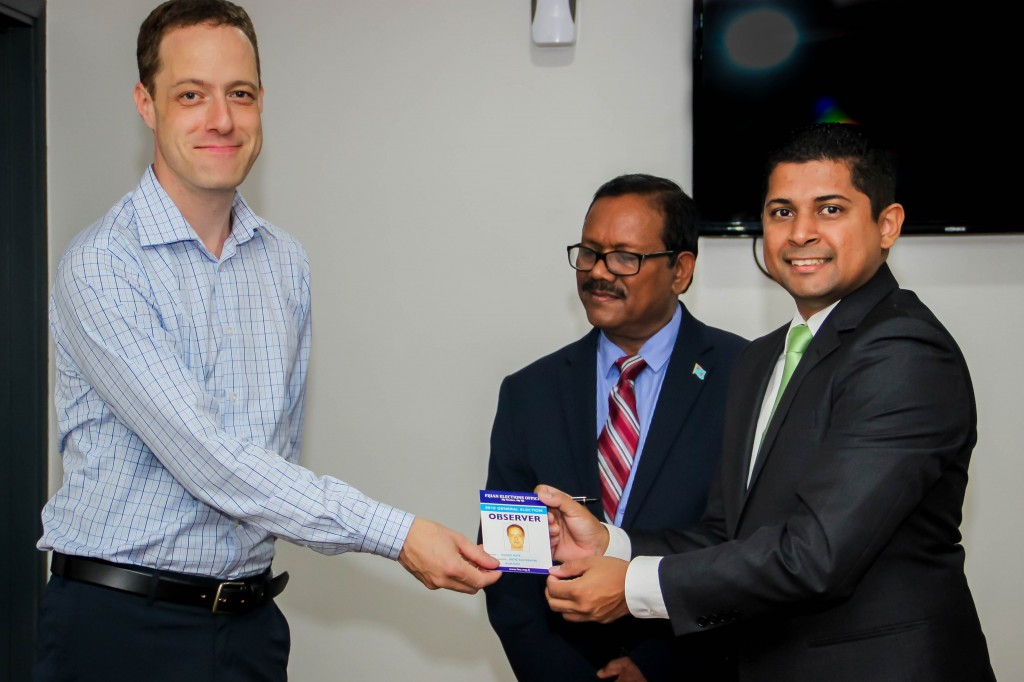 Daniel Kark receiving his accredited ID from Supervisor of Elections, Supervisor  of  Elections,  Mr  Mohammed Saneem
