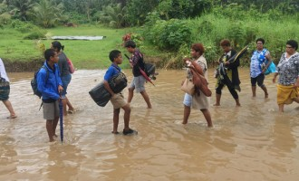 Residents Wade Flooded Road to School, Work