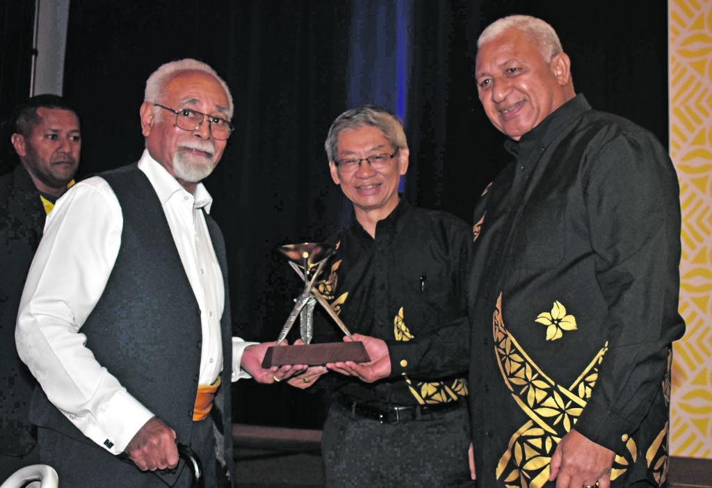 Radike Qereqeretabua receives the award on behalf of late Patrick 'Paddy' Doyle, FHTA Chairman Dixon Seeto, and Prime Minister Voreqe Bainimarama during the 2018 ANZ FETA at the Sofitel Fiji Resort and Spa on Denarau last night. Photo: WAISEA NASOKIA