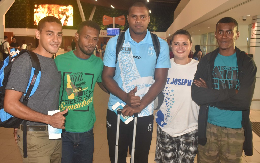 Fiji Airways 7s Josua Vakurinabili with fans at the Nadi International Airport yesterday. Photo: WAISEA NASOKIA