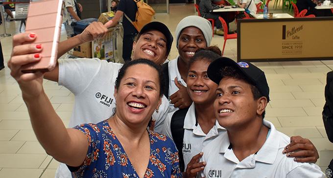 A fan with the Fiji Airways Fijiana 7s reps (left-right) Sereana Nagatalevu, Raijeli Daveua, Tokasa Seniyasi, Lavenia Tinai at Nadi International Airport  on April 24, 2019.  Photo: Waisea Nasokia