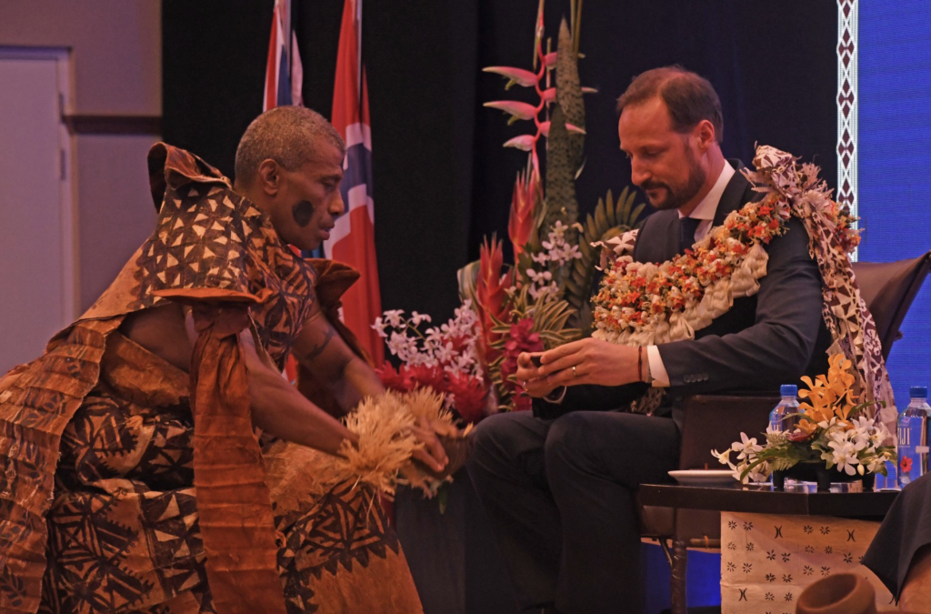The Prince of Norway receives a bowl of kava during the traditional ceremony of welcome.