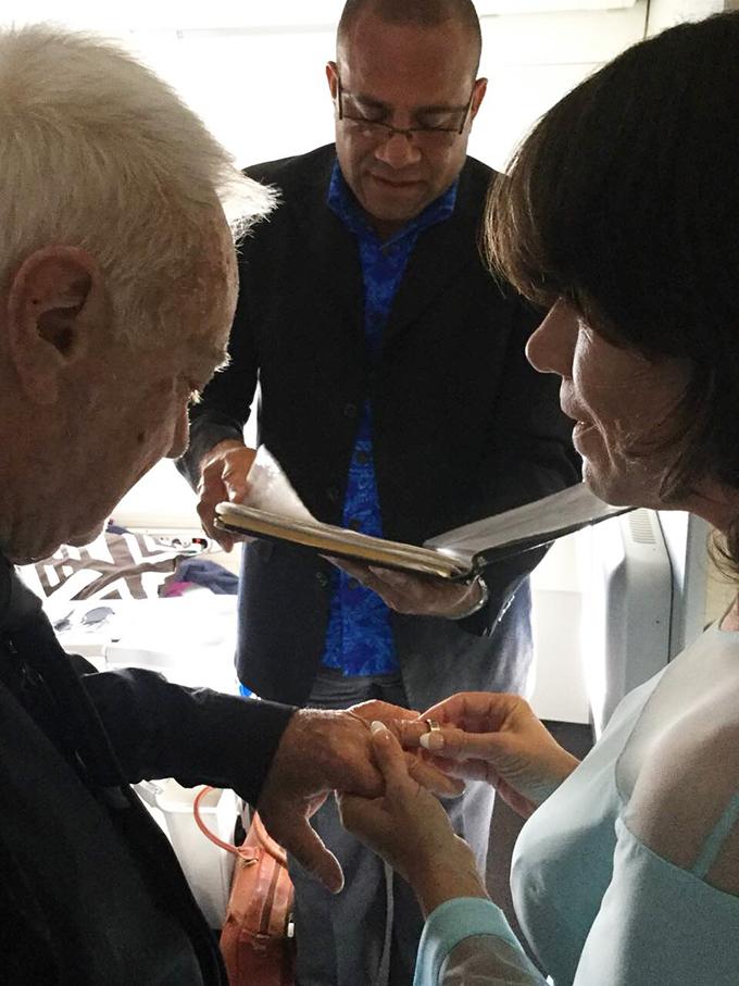 Kylie slips the ring onto Captain Seymour's finger while celebrant Apisai Vasu looks on.