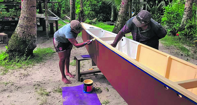 Members of the Uto ni Yalo Trust put the finishing coat on a traditional sailing boat. It is one of 100 they plan to give out to help rural communities.  Photo: Courtesy of Dwain Ah Tong