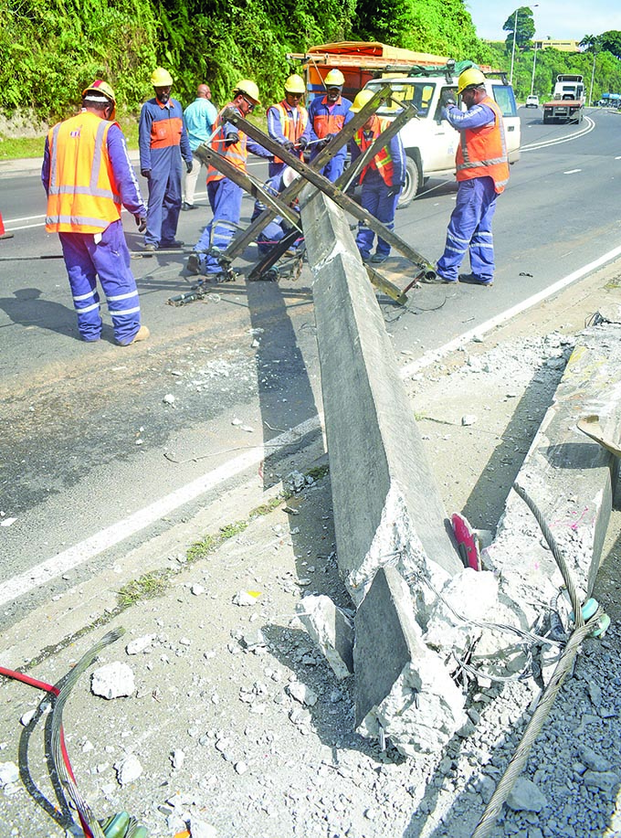 Energy Fiji Limited workers remove the power lines after a Raiwaqa bus driver lost control of the bus he was driving and collided with a EFL power post in Samabula, Suva, on June