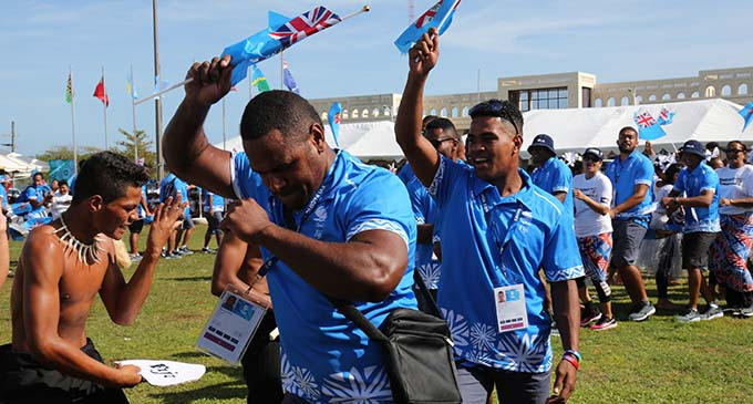 Team Fiji athletes Michael Peters (right) and Penioni Tagituimua of the Fiji Rugby League team celebrate the Pacific Games flag raising ceremony with other Team Fiji athletes and officials on July 6, 2019 with a student of Solosolo Primary School at Falefono, Mulinu'u in Samoa. The Team Fiji contingent, during their stay in Samoa, has been adopted by the students of Solosolo Primary School. The Pacific Games opening ceremony will be held today.  Photo: Anasilini Natoga
