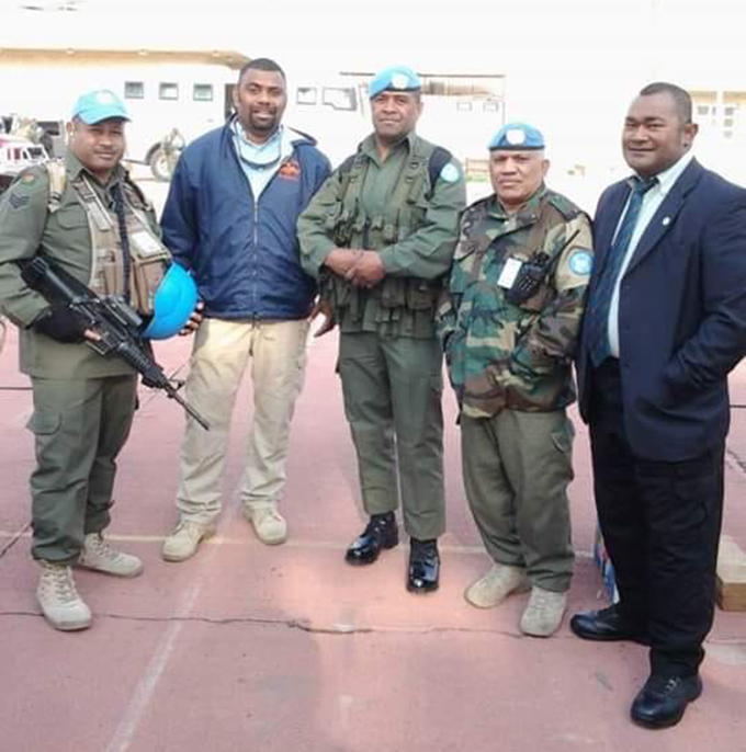 The late Mr Tabuatausole (standing 2nd from the right with blue jacket) with members of the Fiji Contingent serving with the UN Assistance Mission in Iraq, 2006. Photo 1. The late Mr Tabuatausole (standing 2nd from the right with blue jacket) with members of the Fiji Contingent serving with the UN Assistance Mission in Iraq, 2006.