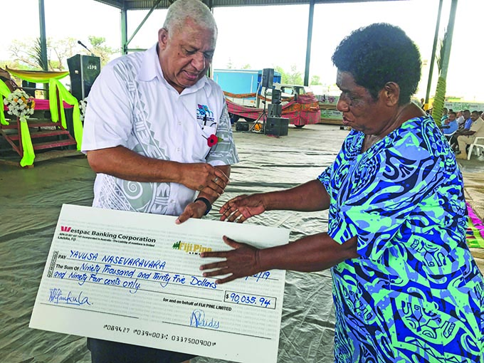 A member of the Yavusa Nasevaravara receiving her checeque from the Prime Minister Voreqe Bainimarama at Tropik Wood yesterday. Photo: Charles Chambers