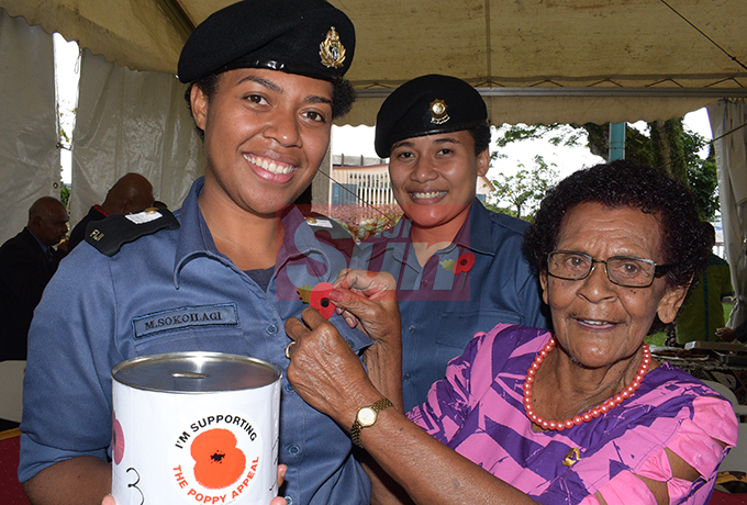 Ecela Vakacokaivalu  80, (right) member of ex-serviceman association pin, the Poppy flowers to MID Meresaini Sokoilagi and OS Jenny Waqa following the launching of Poppy Appeal by President Jioji Konrote and Acting Prime Minister and Minister for Fisheries Semi Koroilavesau at Ratu Sukuna Park on October 4, 2019.Photo: Ronald Kumar.