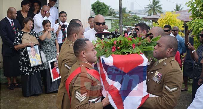Fijian British Army Soldiers carry the casket of late Ifereimi Custine Tui Vasu as the wife, Marian Vasu and daughter, Kiti Vasu (both with photos) at Suvavou Village on December 17, 2019. Photo: Ronald Kumar.