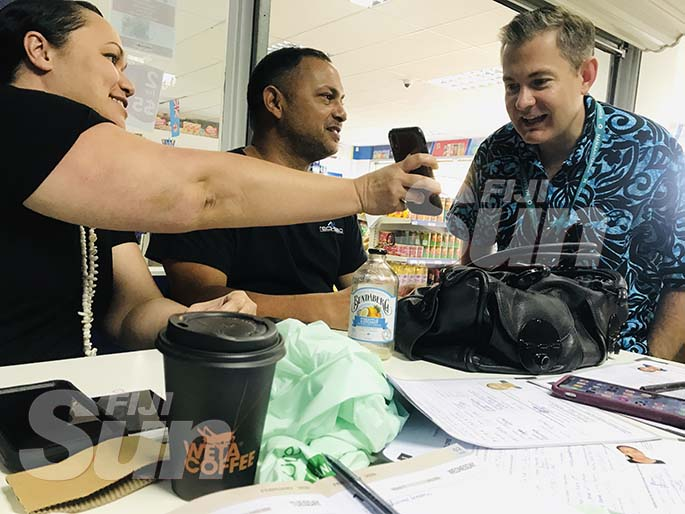 Writers Lodge owners Mue Fisher Bentley with her husband Darran show New Zealand High Commissioner Jonathan Curr a digital copy of his comment in the Fiji Sun's Social Media Watch page. Photo: Frederica Elbourne