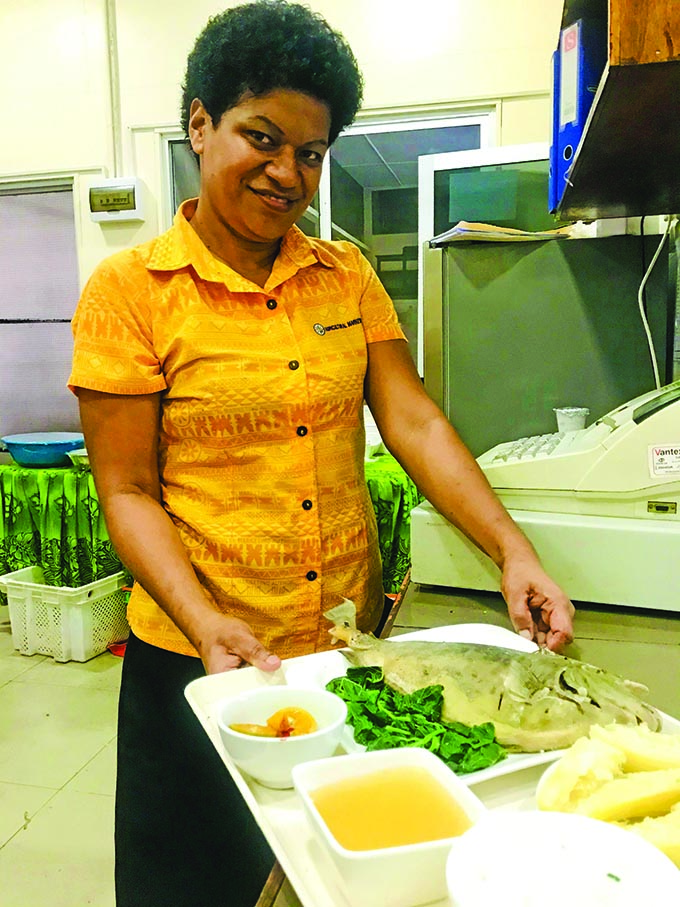 Vasemaca Rokonai displays a serve of boiled fish that's prepared at Sautu restaurant Photo: Frederica Elbourne