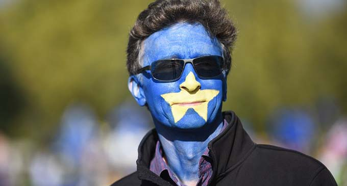 "A protester with his face painted in the colors of an EU flag prepares to attend the ""Together for the Final Say"" event at the Parliament Square in London, Britain, on Oct. 19, 2019. (Photo by Stephen Chung/Xinhua)"