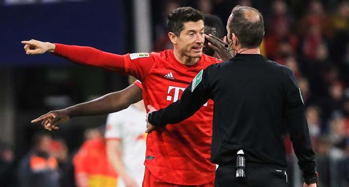 Robert Lewandowski (L) of Bayern Munich complains to the referee during a German Bundesliga football match between FC Bayern Munich and RB Leipzig in Munich, Germany, Feb. 9, 2020. (Photo by Philippe Ruiz/Xinhua)