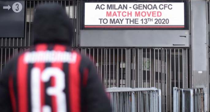 A fan of AC Milan stands outside the San Siro stadium after a Serie A soccer match between AC Milan and Genoa was postponed due to the recent coronavirus outbreak in Milan, Italy, March 1, 2020.(Photo by Alberto Lingria/Xinhua)