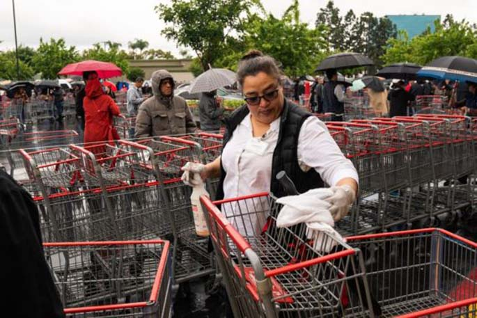 A staff member disinfects the handles of shopping trolleys outside a Costco supermarket in Los Angeles, the United States, March 14, 2020. (Photo by Qian Weizhong/Xinhua)