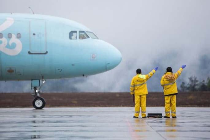 Staff members instruct a departing plane at Wudangshan Airport in Shiyan, central China's Hubei Province, March 29, 2020. (Photo by Tao Debin/Xinhua)