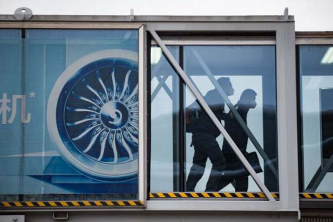 Passengers walk through the jet bridge after arriving at Wudangshan Airport in Shiyan, central China's Hubei Province, March 29, 2020. (Photo by Tao Debin/Xinhua)