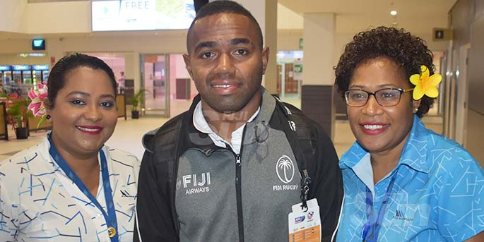 Fiji Airways 7s rep Waisea Nacuqu is flanked by fans Renuka Devi (left) and Inise Kalouarai (right) at the Nadi International Airport on March 11, 2020.  Photo: Waisea Nasokia