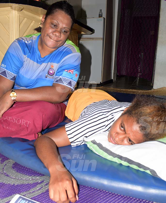 Mereseini Nabou can only relate her story lying down on her bed while her mother, Nanise Baba, looks on.She is unable to sleep on her back that is covered with scars.Photos: Ronald Kumar