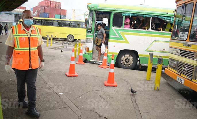 Suva City Council enforcement officer Jope Kete (left) monitors people's movement at Suva bus stand as cone been placed at the bus stand for people to practice social distancing on March 31, 2020. Photo: Ronald Kumar.